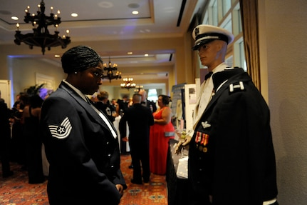 Technical Sgt. Carmeisha Layton takes a closer look at Air Force uniforms displayed during the Joint Base San Antonio Air Force 67th birthday celebration at the Westin Hotel in San Antonio Sept. 20.  The modern day Air Force was created as a separate military service on Sept. 18, 1947, with the implementation of the National Security Act of 1947 under President Truman.  The Air Force's core missions are rooted in its original roles and responsibilities that were assigned in 1947; today the core missions are air and space superiority, intelligence, surveillance and reconnaissance, rapid global mobility, global strike and command and control.(U.S. Air Force photo by  Desiree N. Palacios/Released)