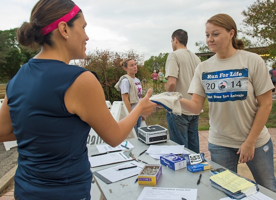 1st. Lt. Jenneva Barrett, 59th Operations Group staff social worker, hands out a T-shirt at the registration table of the 5k Run for Life.(U.S. Air Force photo by Benjamin Faske/Released)