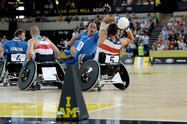 Air Force Staff Sgt. Mark Johnson passes the ball around Italy's Armondo Marco Iannuzzi during the United State's 22-4 victory over Italy in a wheelchair rugby pool match at the 2014 Invictus Games. Invictus Games is an international competition that brings together wounded, injured and ill service members in the spirit of friendly athletic competition. American Soldiers, Sailors, Airmen and Marines are representing the United States in the competition which is being held in London Sept. 10-14. (U.S. Navy photo by Mass Communication Specialist 2nd Class Joshua D. Sheppard/Released)