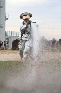 Senior Airman Kelyn Maunu, 802nd Security Forces Squadron patrolman, knocks over a cone with water pressure during the firefighter fitness challenge portion of the Battle of the Badges competition Sept. 27 at Joint Base San Antonio-Randolph's Camp Talon. Firefighters and security forces members from Joint Base San Antonio locations have competed in Battle of the Badges for the past three years. The initiative was designed to build stronger bonds between the agencies and has become a tradition for the unit members, their families and friends. (U.S. Air Force photo by Johnny Saldivar)