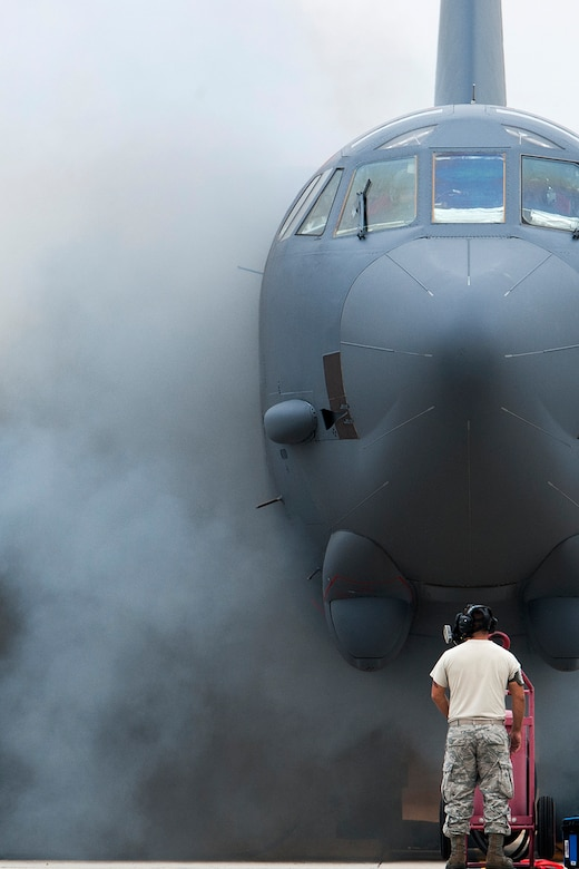 """The wing of a B-52H Stratofortress in obscured by smoke after a """"cart-start"""" of its engines, Sept. 18, 2014, Barksdale Air Force Base, La. This type of engine start enables the aircraft to be airborne within minutes and is routine training for maintenance personnel and aircrew. (U.S. Air Force photo by Master Sgt. Greg Steele/Released)"""
