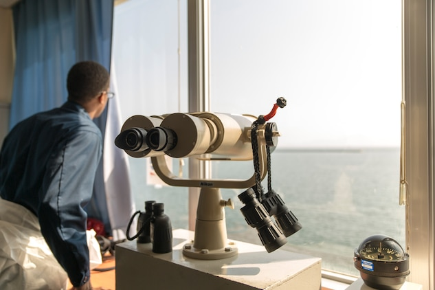 Petty Officer 3rd Class Nicholas Easter, quarter master and navigator with Headquarters and Headquarters Squadron, looks through the window before scanning the area with binoculars, Sept. 29, 2014, at the Iwkauni Harbor aboard Marine Corps Air Station Iwakuni, Japan. Easter's role is to guide various vessels as they venture through the harbor while maintaining security and ensuring environmental safety.
