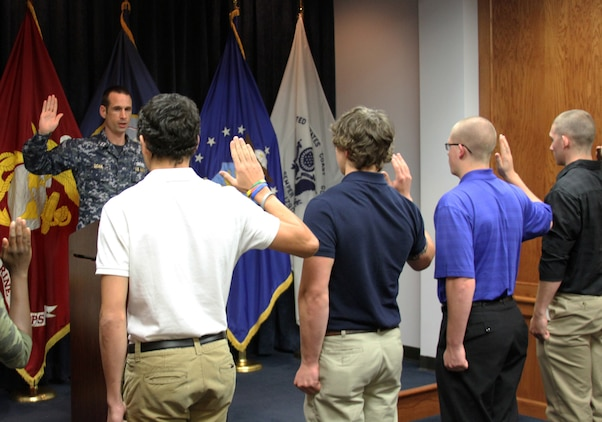 U.S. Navy Lt. Jason Doan, Military Entrance Processing Station Ft. Lee operations officer, administers the Oath of Enlistment to five of the seven Marine Corps applicants who enlisted on the 13th anniversary of Sept. 11, 2001. After years of the Global War on Terror, new recruits enlist to serve their nation almost every day.  (U.S. Marine Corps photo by Cpl. Aaron Diamant/Released)