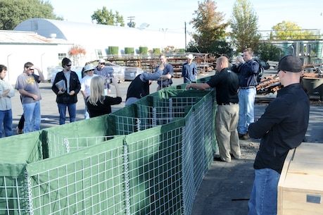 "Employees from the U.S. Army Corps of Engineers Sacramento District assemble portable flood-water barriers during a product demonstration at a Corps facility here Nov. 3. Three new products are being tested by Corps employees for future use in emergency and disaster operations. ""The district has several flood-fighting technologies stored across the nation so we can deploy them when and where we need to,"" said district disaster program manager Christy Jones."