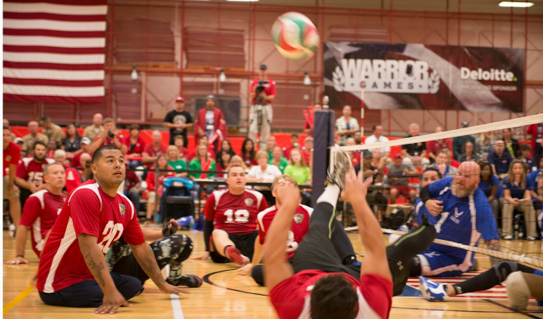 Eric Rodriguez (bottom right), from the Marine Corps volleyball team, tips the ball to teammate Jorge Salazar (middle left) during the teams' volleyball game against Air Force Sept. 29, 2014, at the Warrior Games in Colorado Springs, Colo. The Marines won the first out of three matches with a final of 25-23. (U.S. Marine Corps photo/Cpl. Cuong Le)