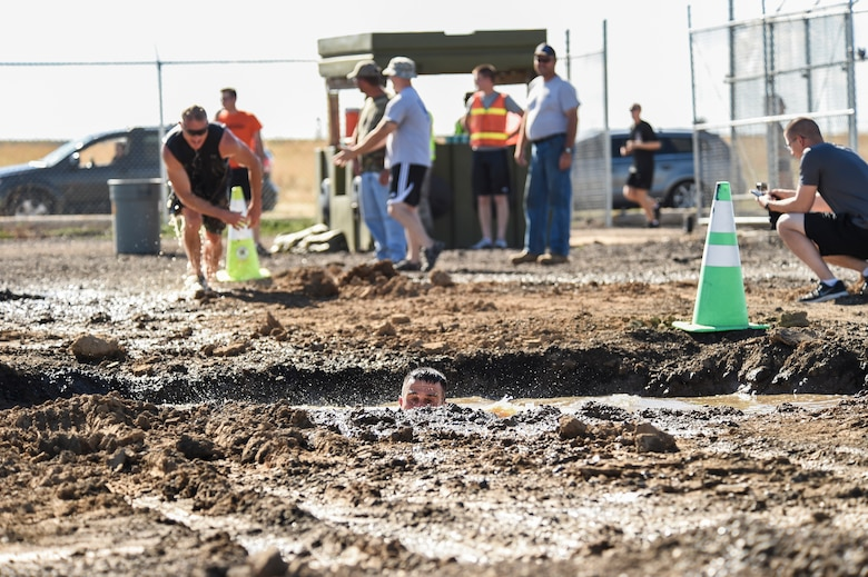 Col. John Wagner, 460th Space Wing commander, swims though a mud pit during WARFIT Sept. 25, 2014, on Buckley Air Force Base, Colo. The 460th Civil Engineer Squadron hosted the September WARFIT, which consisted of a 5K run and a mud obstacle course. WARFIT is a way for the 460th Space Wing and base partner units to get together and stay physically fit. (U.S. Air Force photo by Senior Airman Phillip Houk/Released)