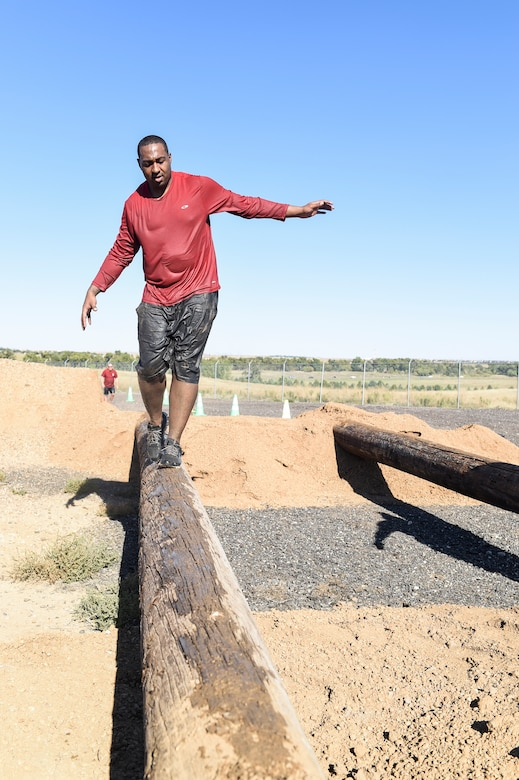 A Team Buckley member makes his way across a wooden beam during WARFIT Sept. 25, 2014, on Buckley Air Force Base, Colo. The 460th Civil Engineer Squadron hosted the September WARFIT, which consisted of a 5K run and a mud obstacle course. WARFIT is a way for the 460th Space Wing and base partner units to get together and stay physically fit. (U.S. Air Force photo by Senior Airman Phillip Houk/Released)
