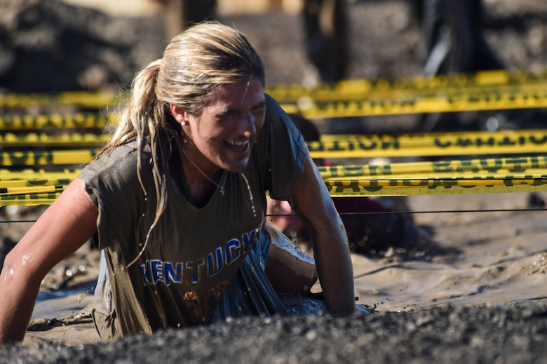 A Team Buckley member finishes the low-crawl obstacle during WARFIT Sept. 25, 2014, on Buckley Air Force Base, Colo. The 460th Civil Engineer Squadron hosted the September WARFIT, which consisted of a 5K run and a mud obstacle course. WARFIT is a way for the 460th Space Wing and base partner units to get together and stay physically fit. (U.S. Air Force photo by Senior Airman Phillip Houk/Released)