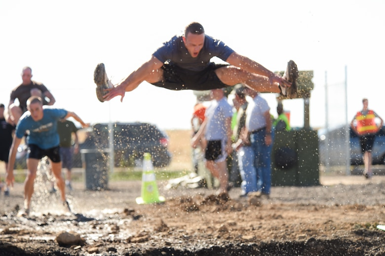 Capt. Luke McPherson jumps into a mud pit during WARFIT Sept. 25, 2014, on Buckley Air Force Base, Colo. The 460th Civil Engineer Squadron hosted the September WARFIT, which consisted of a 5K run and a mud obstacle course. WARFIT is a way for the 460th Space Wing and base partner units to get together and stay physically fit. (U.S. Air Force photo by Senior Airman Phillip Houk/Released)
