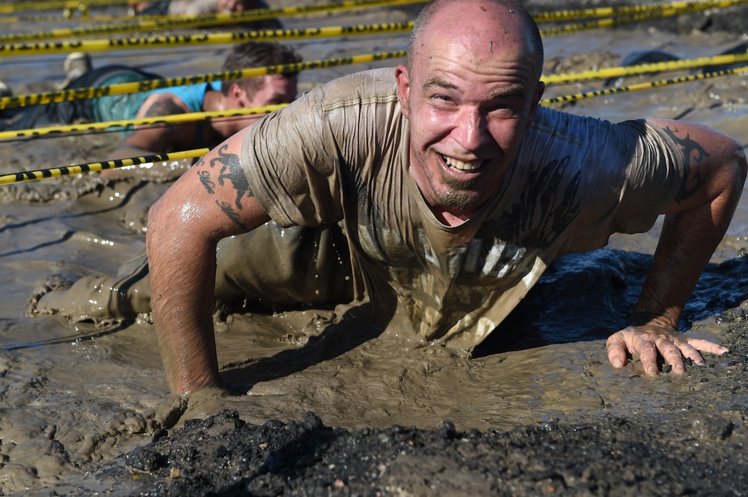 A Team Buckley member emerges from the mud after the low-crawl obstacle during WARFIT Sept. 25, 2014, on Buckley Air Force Base, Colo. The 460th Civil Engineer Squadron hosted the September WARFIT, which consisted of a 5K run and a mud obstacle course. WARFIT is a way for the 460th Space Wing and base partner units to get together and stay physically fit. (U.S. Air Force photo by Airman Emily E. Amyotte/Released)