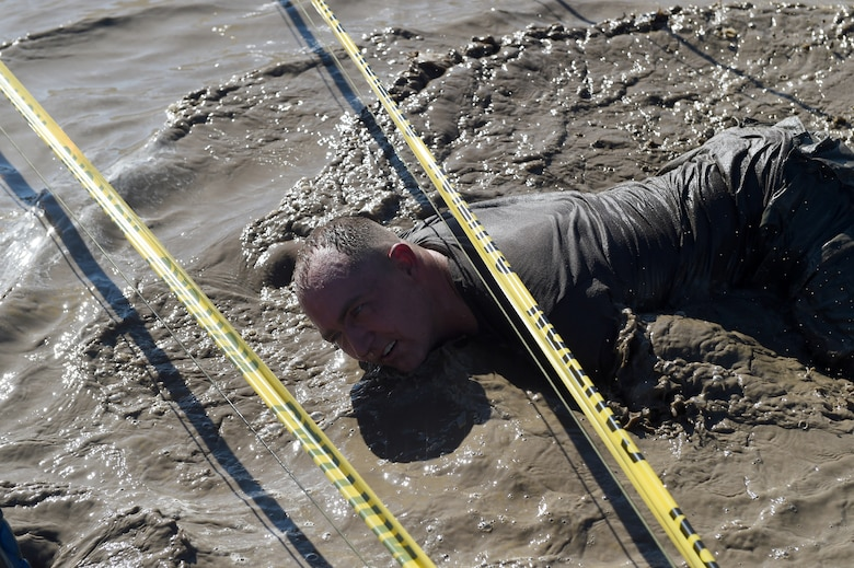 Senior Master Sgt. Shane Enos traverses the low-crawl obstacle during WARFIT Sept. 25, 2014, on Buckley Air Force Base, Colo. The 460th Civil Engineer Squadron hosted the September WARFIT, which consisted of a 5K run and a mud obstacle course. WARFIT is a way for the 460th Space Wing and base partner units to get together and stay physically fit. (U.S. Air Force photo by Airman Emily E. Amyotte/Released)