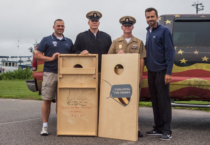 Members of Tailgate for Troops donate corn hole gear to Chief Petty Officer Jeremy Price, a machinist mate assigned to the Naval Consolidated Brig Charleston, and Chief Petty Officer Brad Carman, a gunner's mate assigned to NCBC, Sept. 26, 2014, at Patriots Point in Mount Pleasant, S.C. Tailgate for Troops held a corn hole tournament aboard the U.S.S. Yorktown in downtown Charleston and invited members from all services to participate in the free event. (U.S. Air Force photo/Senior Airman George Goslin)