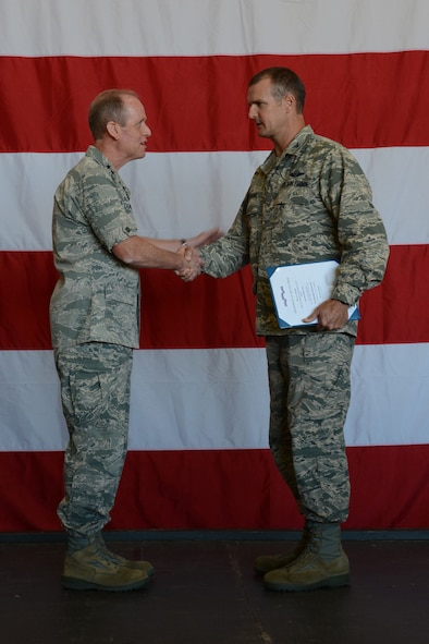 Col. Jeffrey Wiegand, 115th Fighter Wing commander, shakes hands with Maj. Gen. Donald P. Dunbar, adjutant general for Wisconsin, following the acceptance of the 2013 Air Force Outstanding Unit Award certificate during Wingman Day in Hangar 406 in Madison, Wis., Sept. 7, 2014. This is the eighth time the unit has won the award. (Air National Guard photo by Senior Airman Andrea F. Rhode)