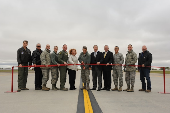 Base and community leaders join Col. Jason Armagost, 5th Bomb Wing commander, as he cuts a ribbon during a ceremony to commemorate the completion of the new runway on Minot Air Force Base, N.D., Sept. 29, 2014. The project began in early April and cost approximately $57 million to complete. The recent construction marks the first replacement of the flightline. (U.S. Air Force photo/Senior Airman Stephanie Morris)