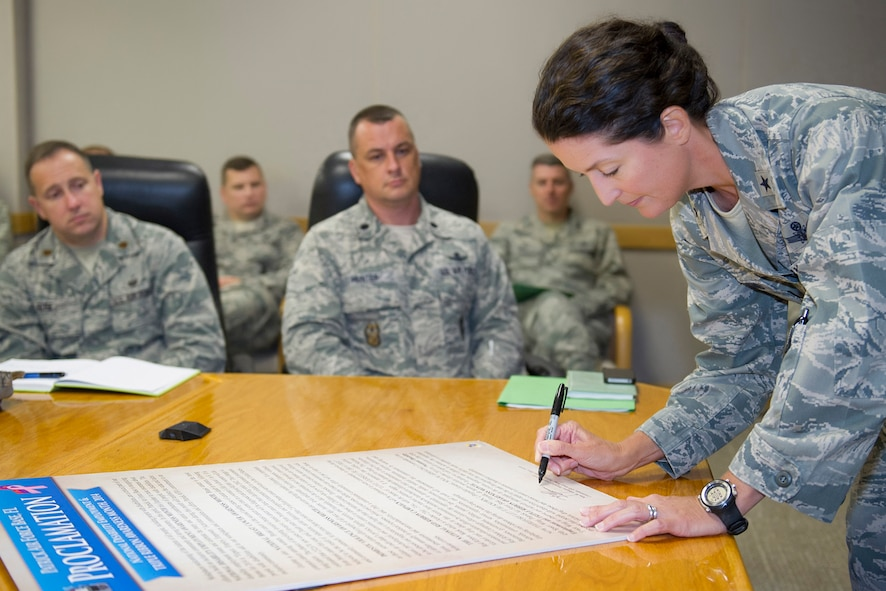 (right) Brig. Gen. Nina Armagno, 45th Space Wing commander, signs a National Disability Employment Awareness Month (NDEAM) and Triple Ribbon Month proclamation, Sept. 17, 2014, at Patrick Air Force Base, Fla. Held each October, NDEAM and Triple Ribbon Month are observed as part of a nationwide annual campaign to raise awareness. (U.S. Air Force photo/Matthew Jurgens)
