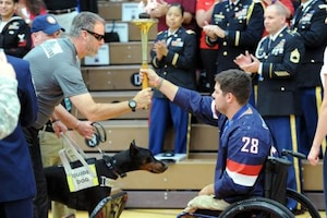 Army Sgt. 1st Class Doug Franklin of the Army Special Operations Command team passes the Olympic torch to retired Marine Corps Cpl. Paul Schaus, who is a gold medal Paralympian, during the opening ceremony for the 2014 Warrior Games at the Olympic Training Center in Colorado Springs, Colo., Sept. 28, 2014. U.S. Army photo by J.D. Leipold