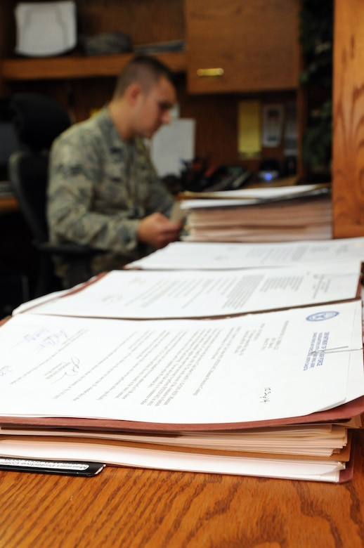 Senior Airman Alexander Ponusky, 319th Contracting Flight contract specialist, reviews paperwork in the 319th CONF office on Grand Forks Air Force Base, N.D., Sept. 25, 2014. The 319th CONF creates and oversees contracts ranging from small purchases of supplies to multimillion dollar construction projects. (U.S. Air Force photo/Staff Sgt. David Dobrydney)