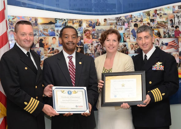 (From left to right) Naval Hospital Jacksonville, Fla., Commanding Officer Capt. John Le Favour, Ph.D.; Assistant Secretary of Defense for Health Affairs Jonathan Woodson, M.D.; Prevention Partners Strategic Alliances Director Annie Thornhill, M.P.H.; and NH Jacksonville Ambassadors for Health Champion Capt. Joseph McQuade, M.D., celebrate NH Jacksonville's Ambassadors for Health Gold Star recognition for achieving the highest national standards for a tobacco-free workplace.