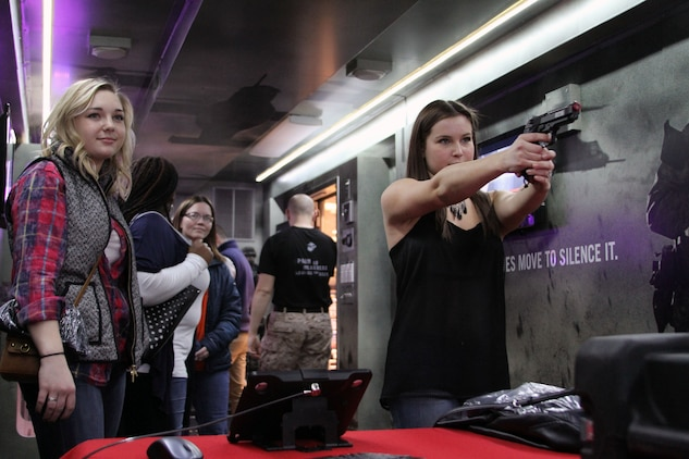 Stephanie Stirm, right, goes through the course of fire on the Indoor Simulated Marksmanship Trainer during the Summit Racing Equipment 49th Annual I-X Piston Powered Auto-Rama, held at the I-X Center in Cleveland, March 22, 2015. Stirm, a native of Stow, Ohio, took the opportunity to show off her shooting skills at the AutoRama that featured a plethora of cars, trucks and motorcycles. The 4th Marine Corps District Enhanced Marketing Vehicle Team was also on hand, bringing their H-1 Hummer and Featherlite trailer to an event that saw tens of thousands of attendees throughout the weekend. (U.S. Marine Corps photo by Sgt. T. M. Stewman/Released)