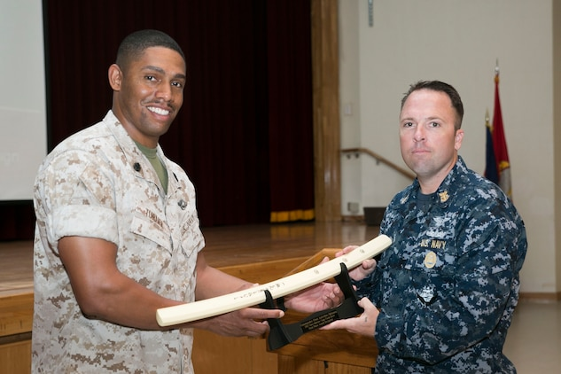 Chief Petty Officer Fred C. Turner, left, presents Master Chief Petty Officer Daniel Irwin, right, with an award recognizing the Commander Fleet Activities Okinawa as one of the two units that raised the most money for last year's Navy-Marine Corps Relief Society Active Duty Fund Drive March 16 at the Camp Foster Community Center. The NMCRS provides financial relief to active duty and retired Marines and sailors as well as their eligible surviving family members through interest-free loans and grants. A large portion of those loans and grants are raised through the ADFD, which gives active duty military a chance to donate and help their fellow service members in need. Turner is the co-coordinator for the Okinawa NMCRS ADFD, and Irwin is the command master chief for Commander Fleet Activities Okinawa.