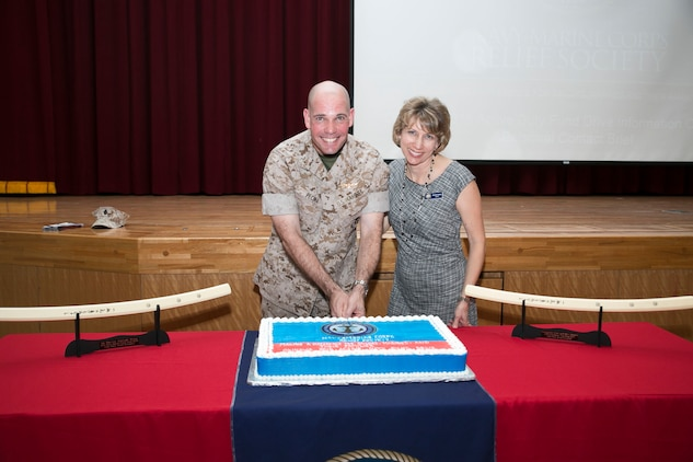 Col. Thomas A. Pecina, left, and Michelle McBride, right, pose for a photo as they cut a cake March 16 at the Camp Foster Community Center during an event commemorating the start of the Okinawa 2015 Active Duty Fund Drive for the Navy-Marine Corps Relief Society. The NMCRS provides financial relief to active duty and retired Marines and sailors as well as their eligible surviving family members through interest-free loans and grants. A large portion of those loans and grants are raised through the ADFD, which gives active duty military a chance to donate and help their fellow service members in need. Pecina is the commanding officer of Headquarters and Support Battalion, Marine Corps Installations Pacific-Marine Corps Base Camp Butler, Japan, and McBride is the director of the Navy-Marine Corps Relief Society, Okinawa office.