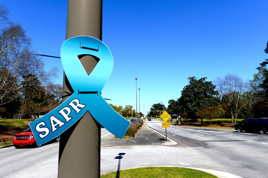 Approximately 10 members from the 628th Civil Engineer Squadron placed teal Sexual Assault Prevention and Response awareness ribbons on light posts at Joint Base Charleston Air Base's front and back gates March 31, 2015. The 628th Air Base Wing declared the month of April 2015 as Sexual Assault Awareness Month for Team Charleston. The teal ribbons symbolize the start of SAAM.  (U.S. Air Force photo by Senior Airman Christopher Reel)
