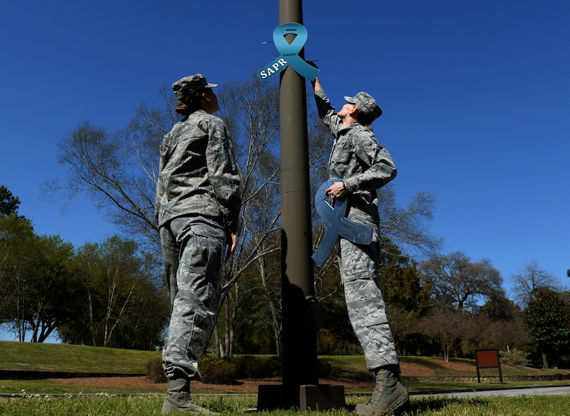 Members from the 628th Civil Engineer Squadron placed teal awareness Sexual Assault Prevention and Response ribbons on light posts at Joint Base Charleston Air Base's front and back gates March 31, 2015. The 628th Air Base Wing declared the month of April 2015 as Sexual Assault Awareness Month for Team Charleston. (U.S. Air Force photo by Senior Airman Christopher Reel)