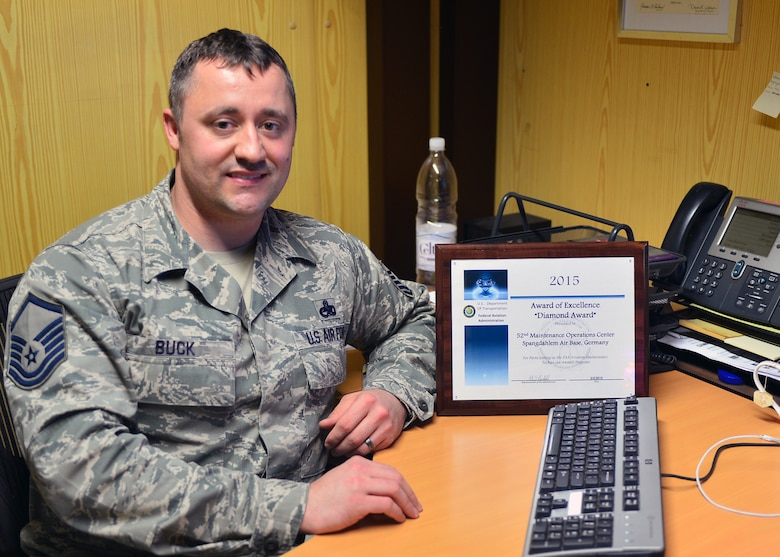 U.S. Air Force Master Sgt. Sean Buck, Maintenance Operations Center superintendent, poses with the MOC's 2015 Diamond Award of Excellence at Spangdahlem Air Base, Germany, March 25, 2015. The MOC was the only active duty Air Force unit to receive the Federal Aviation Administration's highest maintenance training award in 2015. (U.S. Air Force photo by 2nd Lt Meredith Mulvihill/Released)