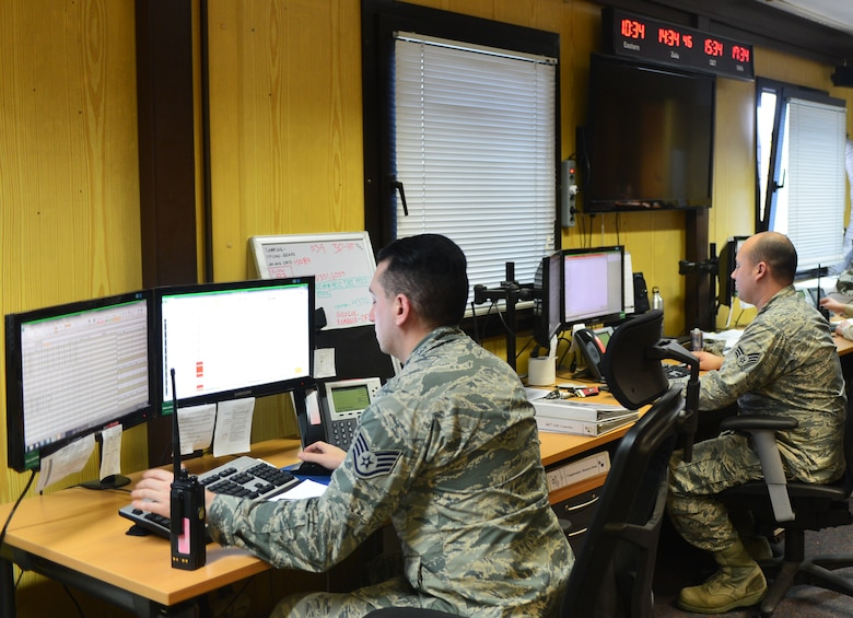 U.S. Air Force Staff Sgt. Curtis Morgan and U.S. Air Force Senior Airman David Hartley, Maintenance Operations Center controllers, monitor flight line operations at Spangdahlem Air Base, Germany, March 25, 2015. The MOC has three eight-hour shifts during the work week to maintain 24-hour operations. (U.S. Air Force photo by 2nd Lt Meredith Mulvihill/Released)