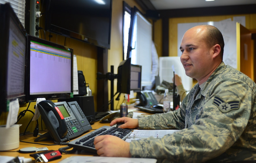 U.S. Air Force Senior Airman David Hartley, a Maintenance Operations Center controller, checks over information in the MOC at Spangdahlem Air Base, Germany, March 25, 2015. Part of the MOC's daily mission is to track the status of all aircraft and equipment on the flight line and coordinate maintenance and logistics support. (U.S. Air Force photo by 2nd Lt Meredith Mulvihill/Released)