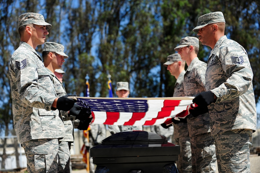 Vandenberg honor guardsmen perform a simulated funeral ceremony during their graduation ceremony April 1, 2015, Vandenberg Air Force Base, Calif. The graduation performance included a flag detail, rifle volley and pallbearers for friends, family and unit commanders. (U.S. Air Force Photo by Staff Sgt. Jim Araos/Released)