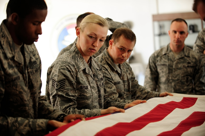 Staff Sgt. April Spilde, U.S. Air Force Honor Guard training instructor, trains new honor guardsmen how to perform a flag folding detail March 25, 2015, Vandenberg Air Force Base, Calif. Members of the Air Force Honor Guard from Joint Base Anacostia-Bolling, D.C. regularly provide specialized training to base level honor guard members. (U.S. Air Force photo by Staff Sgt. Jim Araos/Released)