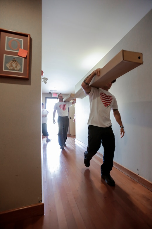 Members of the 138th Fighter Wing (FW) carry bed frames to waiting bedrooms March 29, 2015, at the Ronald McDonald House of Tulsa.  Volunteers from the 138th Fighter Wing assisted at the house upon the arrival of a large shipment new beds and mattresses. (U.S. National Guard photo by Master Sgt. Mark A. Moore/Released)