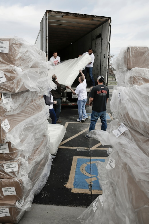 Members of the 138th Fighter Wing (FW) unload a semi-truck of bed frames and mattresses March 29, 2015, at the Ronald McDonald House of Tulsa.  Volunteers from the 138th Fighter Wing assisted at the house upon the arrival of a large shipment new beds and mattresses. (U.S. National Guard photo by Master Sgt. Mark A. Moore/Released)