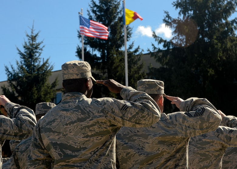 A flight of U.S. Air Force Airmen salute the U.S. and Romanian flags during the opening ceremony of Dacian Thunder 2015 at Campia Turzii, Romania, April 1, 2015. The U.S. and Romanian air forces will conduct training aimed to strengthen interoperability and demonstrate the countries' shared commitment to the security and stability of Europe.  (U.S. Air Force photo by Staff Sgt. Joe W. McFadden/Released)