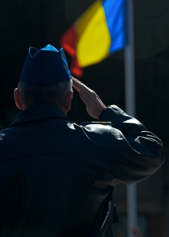 Romanian air force Capt. Cmdr. Caline Hulea, a MiG-21 aircraft pilot assigned to the 711th Fighter Squadron, salutes the raising of the Romanian flag during the opening ceremony of Dacian Thunder 2015 at Campia Turzii, Romania, April 1, 2015. The U.S. and Romanian air forces will conduct training aimed to strengthen interoperability and demonstrate the countries' shared commitment to the security and stability of Europe.  (U.S. Air Force photo by Staff Sgt. Joe W. McFadden/Released)