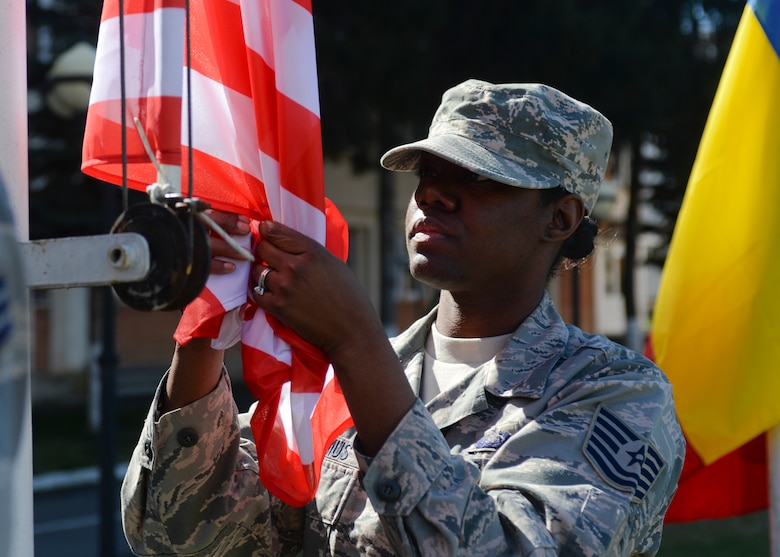 U.S. Air Force Tech. Sgt. Fallon Cornelius, a client systems technician assigned to the 354th Expeditionary Fighter Squadron, unfurls an American flag during the opening ceremony of Dacian Thunder 2015 at Campia Turzii, Romania, April 1, 2015. Cornelius and 300 fellow Airmen and support equipment from the 355th Fighter Wing at Davis-Monthan Air Force Base, Arizona, and the 52nd Fighter Wing at Spangdahlem Air Base, Germany, will support the theater security package as part of Operation Atlantic Resolve. (U.S. Air Force photo by Staff Sgt. Joe W. McFadden/Released)