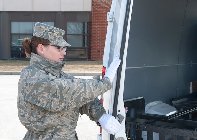 Senior Airman Jamie Debbrecht, a 512th Memorial Affairs Squadron services specialist, practices her role as door guard prior to the start of a dignified transfer divert exercise March 19, 2015, at New Castle Air National Guard Base, Del. Debbrecht is deployed to Air Force Mortuary Affairs Operations from the 512th Memorial Affairs Squadron, Dover Air Force Base, Del. (U.S. Air Force photo/Senior Airman Jared Duhon)