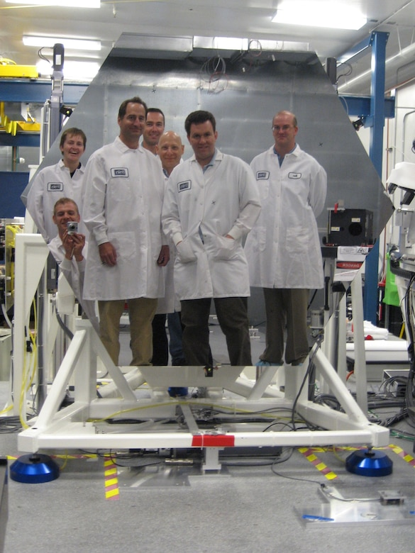 NASA scientist take a picture of themselves in a prototype 1.4 meter diameter beryllium mirror for the James Webb Space Telescope, September 2008.  (Photo courtesy of NASA.gov)