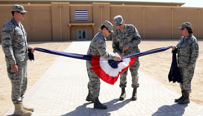U.S. Air Force Col. Caroline Miller, 379th Expeditionary Mission Support Group commander, and Brig. Gen. Darren Hartford, 379th Air Expeditionary Wing commander, cut the ceremonial linen during a linen cutting ceremony, April 3, 2015, at Al Udeid Air Base, Qatar. The linen cutting ceremony symbolized the opening of the new Phase II dormitories in the Blatchford-Preston Complex. (U.S. Air Force photo by Senior Airman Kia Atkins)