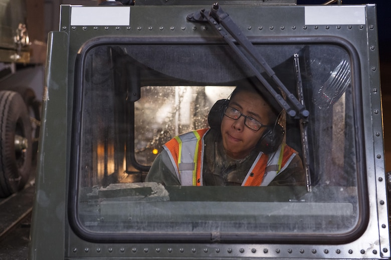 An Airman operates a Tunner 60K aircraft cargo loader while conducting Rapid Raptor program training on Joint Base Elmendorf-Richardson, Alaska, March 26, 2015. The training exercised Rapid Raptor capabilities to quickly deploy a package of combat-ready F-22 Raptors and C-17 Globemaster IIIs loaded with supporting personnel and equipment to any forward operating base in the world. The Airman is assigned to the 773rd Logistics Readiness Squadron. (U.S. Air Force photo/Alejandro Pena)