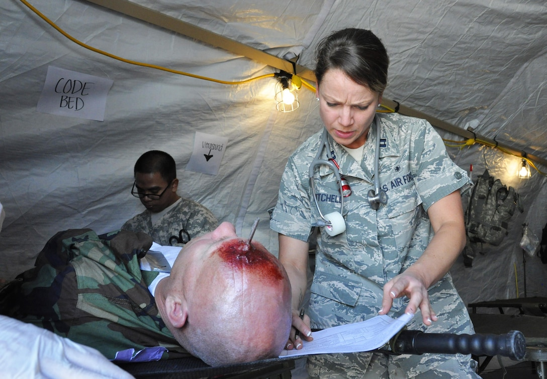 Capt. Diana Mitchell, a medical officer assigned to the 926th Aerospace Medical Squadron, assesses simulated injuries on Master Sgt. Frank Preuss during a mass casualty exercise at Camp C.O.B.R.A., Mar. 27, 2015 at Nellis Air Force Base, Nev. The exercise helped medical personnel handle stressful situations with minimal resources.  (U.S. Air Force photo by Tech. Sgt. Colleen Urban)