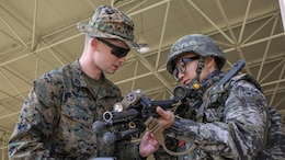 U.S. Marine Corps Lance Cpl. Thomas Harding shows a Republic of Korea Marine his M27 infantry automatic rifle during Korean Marine Exchange Program 15 in the vicinity of Pohang, South Korea, March 29, 2015. The 31st Marine Expeditionary Unit participated in KMEP 15. The overall objective of KMEPs are to enhance amphibious operations between ROK and U.S. forces that contributes to security and stability on the Korean Peninsula as well as the entire Asia-Pacific region.  The ROK Marines are with 33rd Battalion, 1st ROK Marine Division, and the U.S. Marines are with Company E, Battalion Landing Team 2nd Battalion, 4th Marines, 31st MEU.