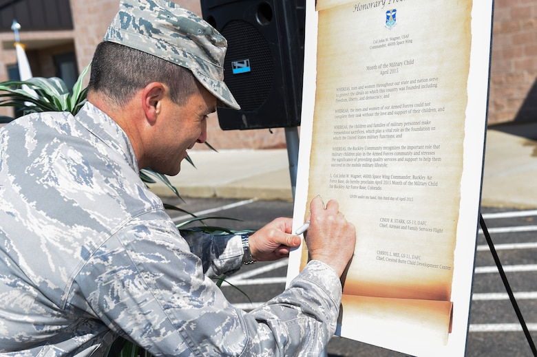 Col. John Wagner, 460th Space Wing commander, signs the Month of the Military Child honorary proclamation April 3, 2015, at the Crested Butte Child Development Center on Buckley Air Force Base, Colo. The proclamation officially cited April as Month of the Military Child. (U.S. Air Force photo by Airman 1st Class Samantha Saulsbury/Released)