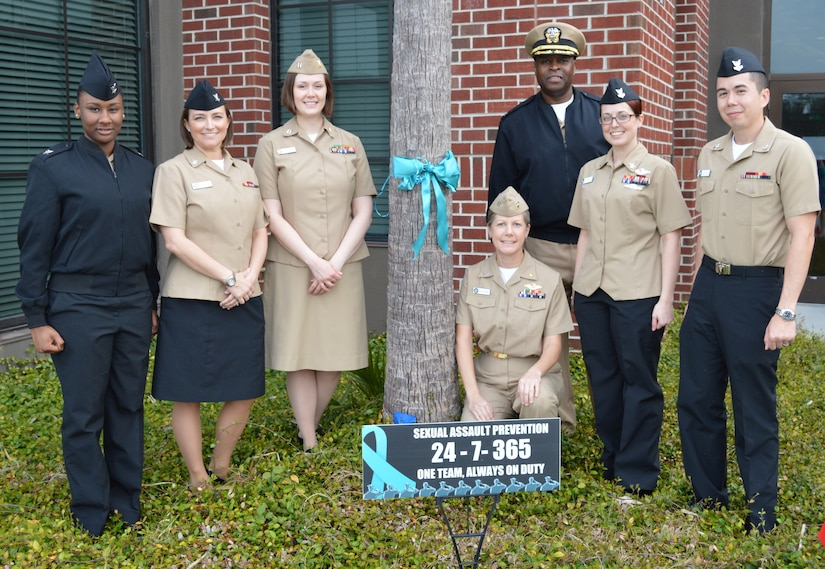 Naval Health Clinic Charleston Sexual Assault Prevention and Response representatives pose near a teal ribbon tied to tree in front of NHCC April 3 on Joint Base CHarleston, S.C., in honor of Sexual Assault Awareness Month. From left to right: Petty Officer 3rd Class Amanda Abrams, Petty Officer 3rd Class Nicole Johnson, Lt. Nikki Pritchard, Lt. Kristin Aucker, NHCC Commanding Officer Capt. Marvin Jones, Petty Officer 2nd Class Michele Coltrane and Petty Officer 2nd Class John Betts. (U.S. Navy photo/Kris Patterson)