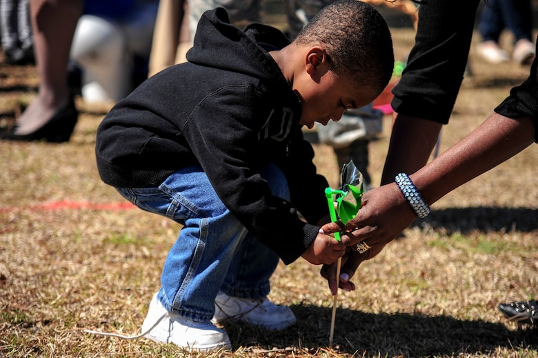 "Members of Team Seymour plant pinwheels during a ""Pinwheels for Child Abuse Prevention"" event, April 1, 2015, at Seymour Johnson Air Force Base, North Carolina. The pinwheel stands as a symbol of hope for children across that nation that they will never endure abuse or neglect. (U.S Air Force photo/Senior Airman Brittain Crolley)"