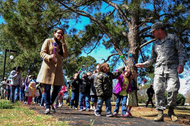 "Col. Mark Slocum, 4th Fighter Wing commander, and his wife, Xavi, lead children on a walk to the pinwheel garden during a ""Pinwheels for Child Abuse Prevention"" event, April 1, 2015, at Seymour Johnson Air Force Base, North Carolina. The campaign works to ensure the healthy development of children nationwide. (U.S Air Force photo/Senior Airman Brittain Crolley)"
