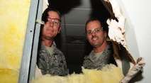 Maj. Joe Pulliam (left), 709th Munitions Squadron commander, Maj. Matthew Drossner, 509th Munitions Squadron commander, met to demolish the wall in the leadership section of their command building at Whiteman Air Force Base, Mo., March 19, 2015. The demolition of the wall signified the merger of the two units. The new combined squadron will be renamed to the 509th Munitions Squadron. Renovations of the new office are scheduled to be accomplished by June 22. (U.S. Air Force photo by Staff Sgt. Nick Wilson/Released)