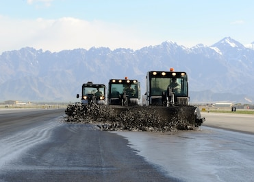 U.S. Air Force Airmen assigned to the 577th Expeditionary Prime Base Engineer Emergency Force Squadron remove built-up rubber from a runway using bobcats equipped with bristled rollers April 4, 2015 at Bagram Airfield, Afghanistan. Forward deployed from Southwest Asia, 577 EPBS Airmen travel throughout the Air Force Central Command area of responsibility completing projects to facilitate mission accomplishment. At BAF, the Airmen remove rubber from 30,000 – 40,000 square feet of runway each day, and will cover a total of 382,000 square feet before redeploying. (U.S. Air Force photo by Staff Sgt. Whitney Amstutz/released)