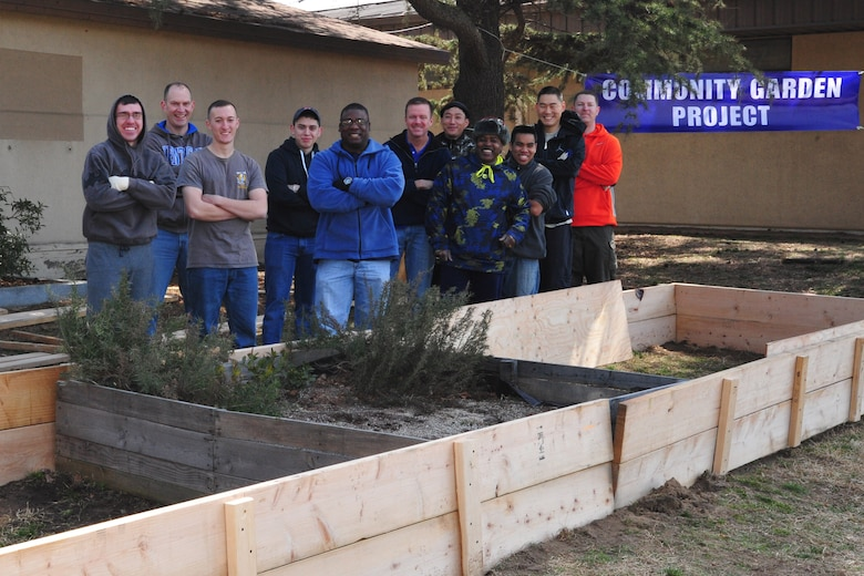"8th Fighter Wing Airmen pose for a group photo after building the initial portion of the foundation for ""Wolf Pack Garden"" in front of the Sonlight Inn, March 14, 2015, at Kunsan Air Base, Republic of Korea. The garden is part of a community initiative to promote healthy living for Wolf Pack Airmen. (U.S. Air Force photo by Capt. Reba Good/Released)"